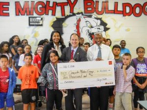 Steven Schultz, Area President ,Senior Vice President at Wells Fargo is flanked by a host of KidsCode kids, Machelle Maner  Vice President, Community Development at Wells Fargo (left), and Ralph Smith, Director and Founder of Computer Mentors (right).